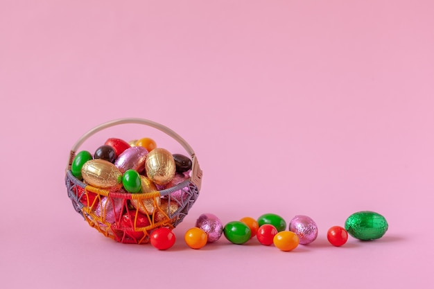 Сладкие пасхальные яйца в корзине на розовом