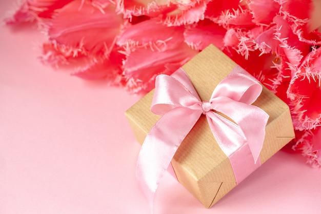 ピンクの背景のピンクのチューリップの花の美しい花束とプレゼントやギフトボックス。