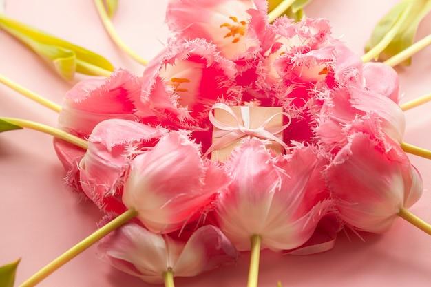 ピンクのチューリップの花でクラフトペーパーとピンクの弓で包まれたギフトボックス。