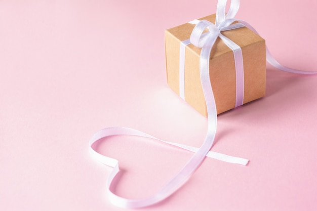 ピンクの背景に白いリボンのギフトまたはプレゼントボックス。