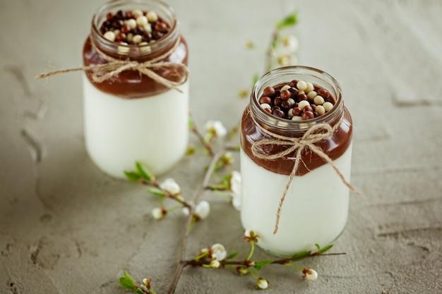 Стакан домашнего йогурта с шоколадным муссом и шоколадных конфет падает с весны ветви на бетонном фоне.