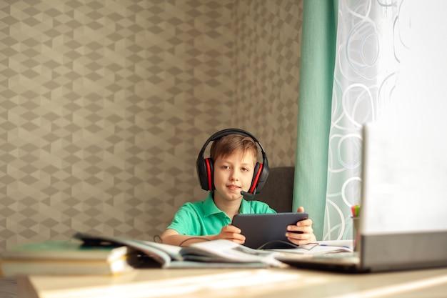 ヘッドフォンで遠隔学習の子供がタブレットでレッスンを見ています。コンセプトオンライン教育。