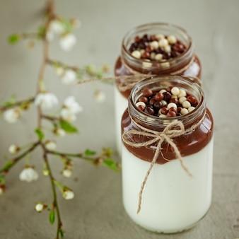 Стакан домашнего йогурта с шоколадным муссом и шоколадные конфеты капли с весенней ветвью.