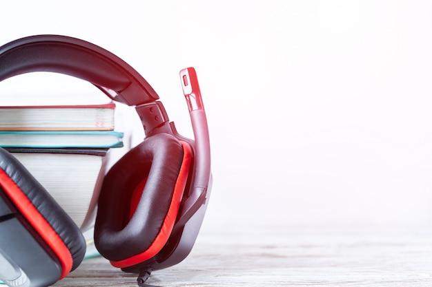 現代のヘッドフォンと白い背景の上のテーブルの上の本。オーディオブックのコンセプトです。