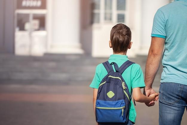 父は小さな子供学校の男の子を率いて手をつないで行きます。背中の後ろにバックパックを持つ親と息子。