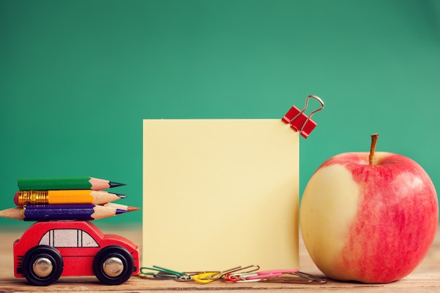 木製のテーブルとテキストのための場所にカラフルな鉛筆と赤いリンゴを運ぶミニチュア赤い車