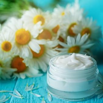 カモミールの花またはボディと青い木製のテーブルの上の顔の化粧品クリーム