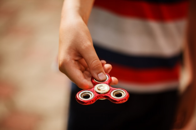 Школьник держит в руках вертушку. модная и популярная игрушка для детей и взрослых.