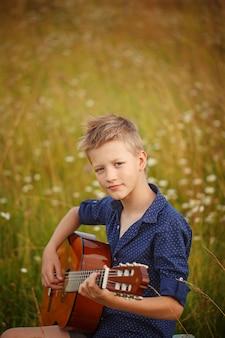 ハンサムなかわいい男の子は屋外でアコースティックギターで遊んでいます。