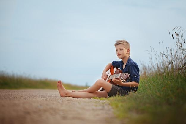 ハンサムなかわいい男の子は夏の日のアコースティックギターの上に座って道を遊んでいます。