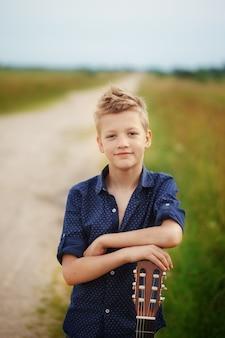 ハンサムなかわいい男の子は屋外でアコースティックギターを持っています。