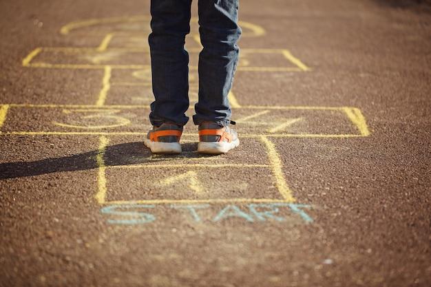 屋外の遊び場で石蹴りを遊んでいる子供たち。石けりポピュラーストリートゲーム