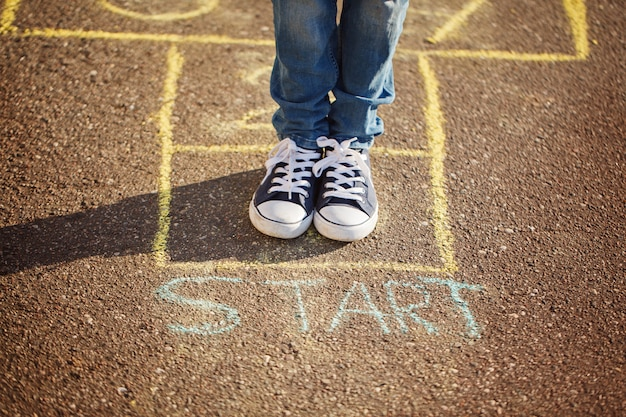少年の足と屋外の遊び場で石蹴りを遊んでのクローズアップ。石けりポピュラーストリートゲーム