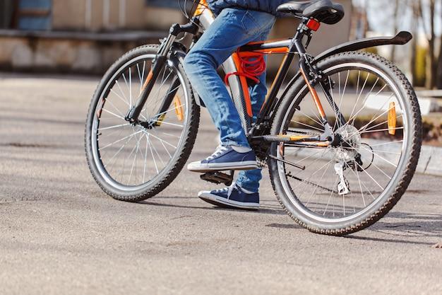晴れた春の日にアスファルトの道路で自転車に乗る子。