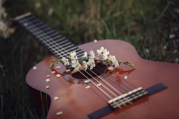 草の上に横たわるギター。コンセプト:春と愛の歌。調色画像