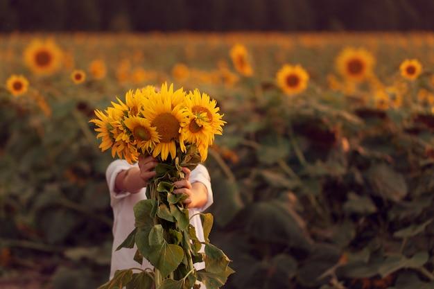 日没の夏のひまわり畑の美しいヒマワリの花束と幸せな子。