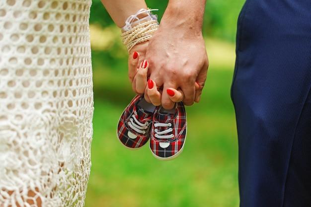 手と小さな靴のペアを保持している将来の両親は、緑豊かな背景をやり過ぎます。