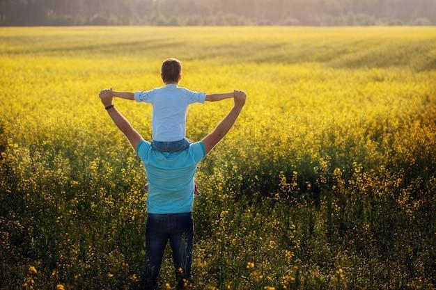 父は彼の息子を抱きしめると夏の自然の背景に立っています。