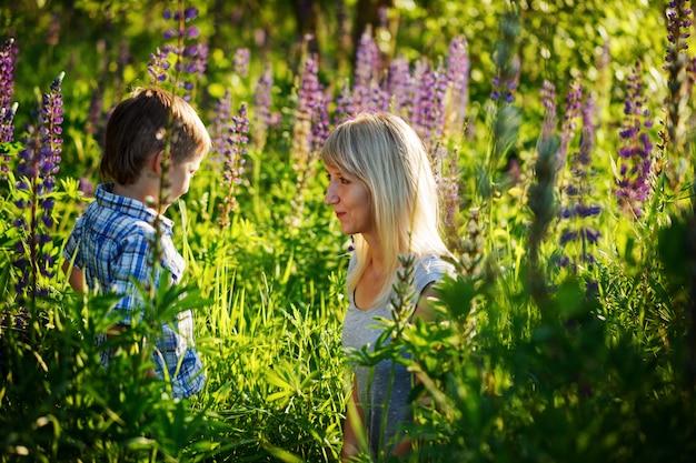 Прелестный ребенок и мама в парке весной, цветок и подарок.