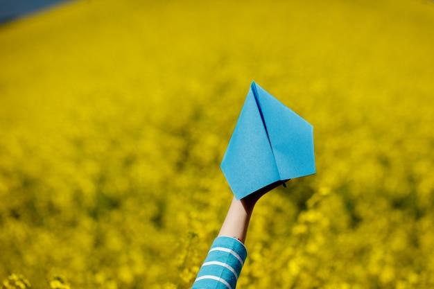 子供たちの紙飛行機は黄色の背景に手します。