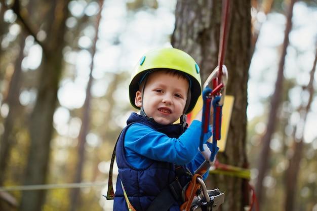 Счастливый маленький мальчик, с удовольствием на открытом воздухе, играя и делая деятельность