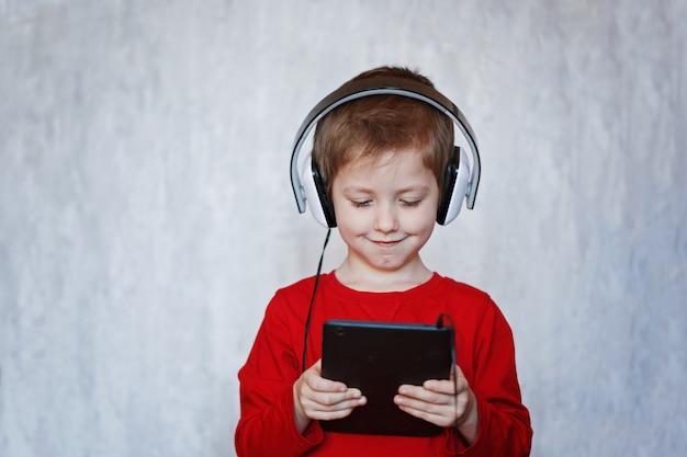Маленький мальчик слушает музыку со своего планшета на наушниках