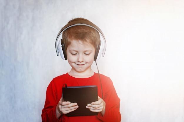 Маленький мальчик с гарнитурой с помощью сенсорной панели, раннего образования и игры