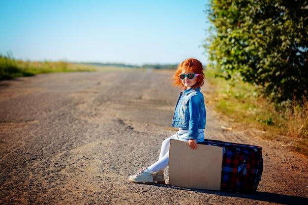 Довольно маленькая кудрявая девушка сидит на чемодане на дороге и ждет автобус или автомобиль в солнечный день.