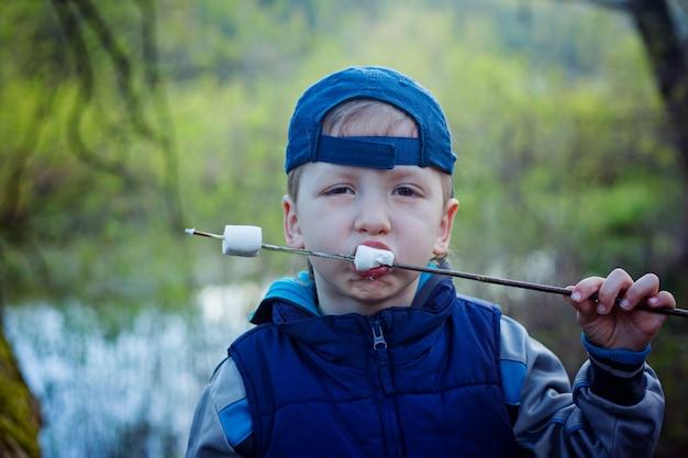 焼きマシュマロを食べるためのクローズアップの肖像画の男の子