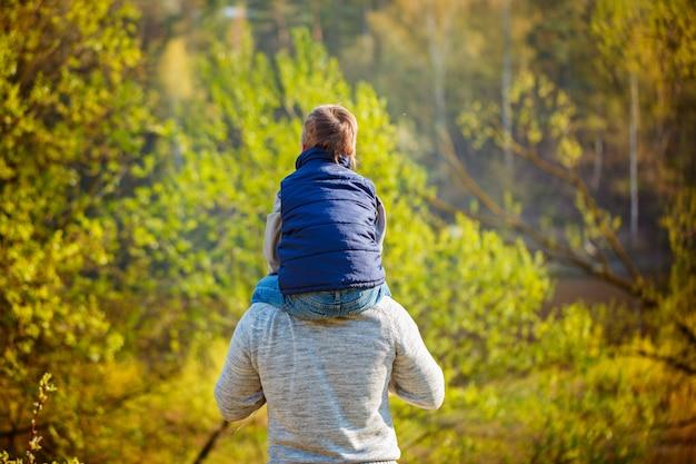 Задний взгляд отца его сын на плечах на природе.