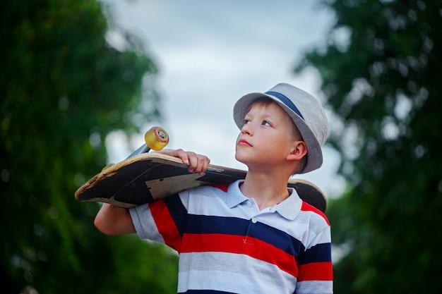 屋外スケートボードを手で保持しているかわいい男の子。キャップとスタイリッシュな服を着ています。