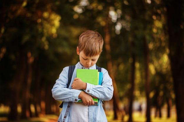 Маленький мальчик, возвращаясь в школу. ребенок с рюкзаком и книгами.