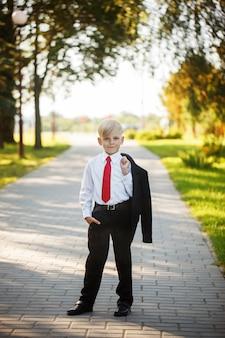 自然の背景にビジネススーツと赤いネクタイを着て小さな男の子