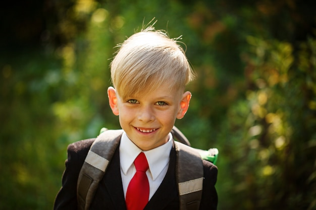 笑顔の瞳孔のクローズアップの肖像画。かわいい男の子が学校に戻る。最初の学校日のバックパックを持つ子供。