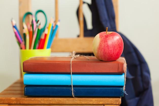Фон обратно в школу с кучей книг и красное яблоко.