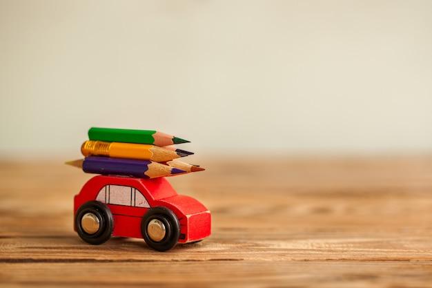 Миниатюрный красный автомобиль, перевозящих красочные карандаши на деревянный стол. вернуться к школьной концепции