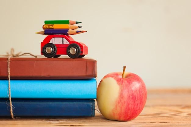 Назад к концепции школы с стогом книг и красного яблока и миниатюрного автомобиля нося красочный карандаш.