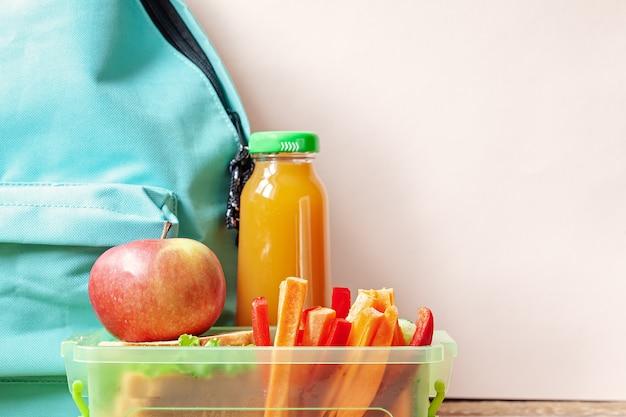 サンドイッチ、野菜、ジュース、アーモンドのテーブルの上の学校のお弁当箱。