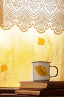 紅茶またはコーヒー、および雨の窓に黄色の葉のカップ