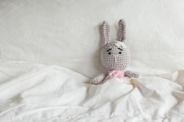白い寝室で頭の上に石膏を持つ病気灰色おもちゃウサギ。