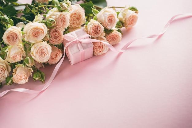 ピンクのバラの花とプレゼントまたはプレゼントボックスピンクの背景。母の日、誕生日、バレンタインデー、レディースデーコンセプト。
