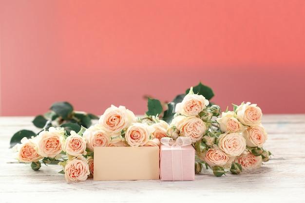 ピンクのバラの花とギフトまたはプレゼントボックスピンクの背景。