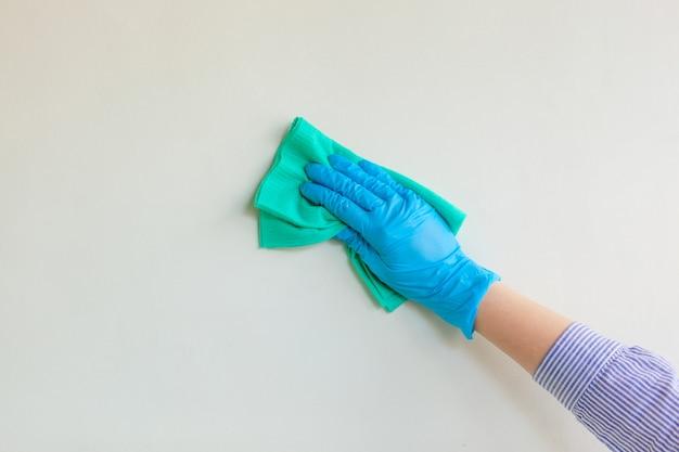 従業員は青いゴム製保護手袋を着用して、乾いた布で壁を壁から拭きます。