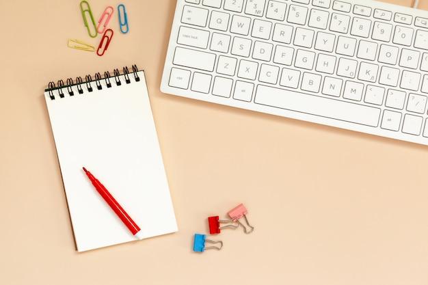 Рабочее место пустая спиральная тетрадь с клавиатурой на столе.