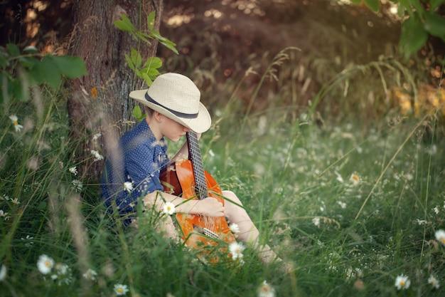 Прелестный мальчик с гитарой, отдыхая в парке. малыш сидит на траве в летний день