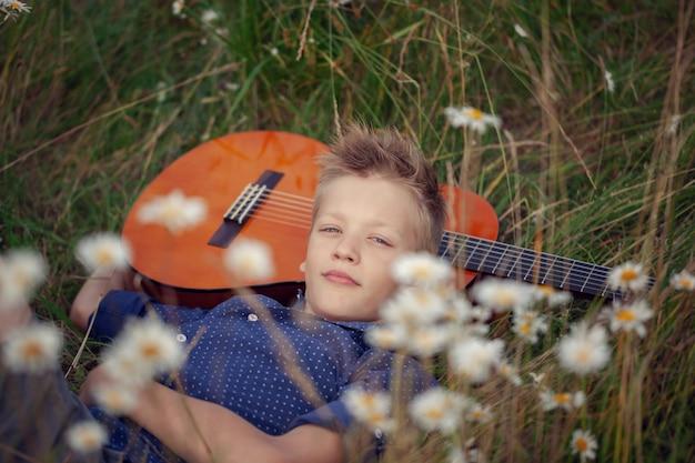 Прелестный мальчик с гитарой, отдыхая в парке. малыш лежал на траве в летний день