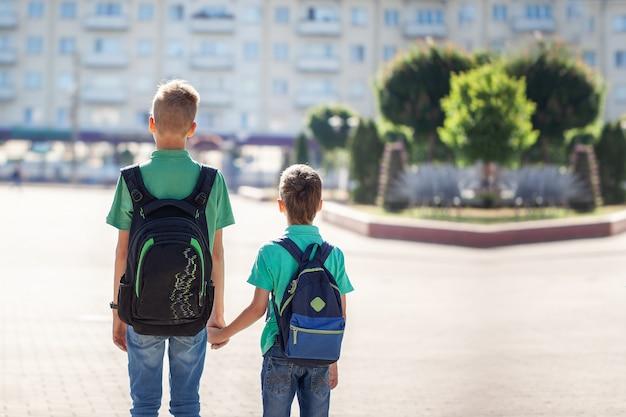 学校に行くバックパックを持つ男子生徒。市内の子供と教育。