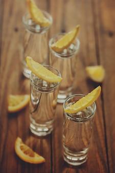 木製の背景にレモンとウォッカのグラス。調色画像です。