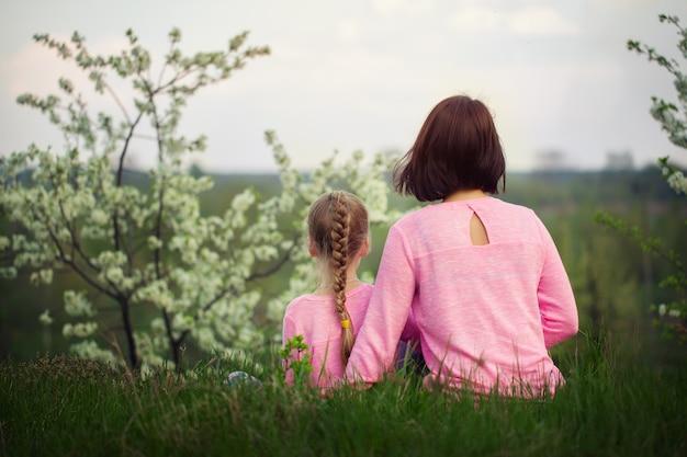Маленькая девочка и ее мать, сидя на траве в летний день. вид со спины.