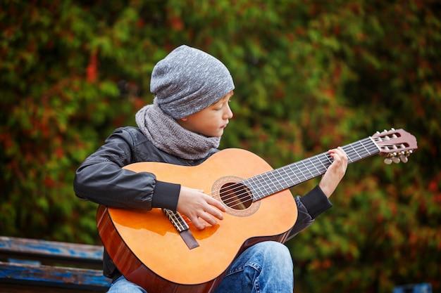 Маленький мальчик играет на гитаре на природе